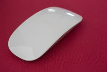Close-up Of White Wireless Mouse On Red Fabric