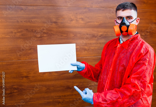 Photo Portrait of a doctor in a red protective suit wearing a protective mask against the disease