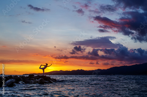 Valokuva Woman practices yoga at seashore