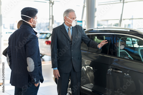 Obraz Young family talking to the salesman and choosing their new car in a showroom during coronavirus pandemic - fototapety do salonu