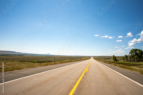 A point of view perspective of a vehicle traveling on a rural road with clouds and blue sky. - 349986489