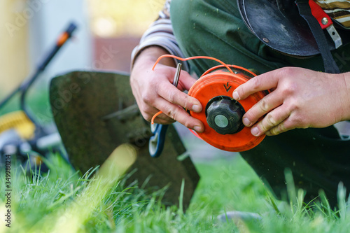 Fototapeta Close up on string trimmer head unknown caucasian man holding and repairing weed cutter replacing parts replacement in day on the field farmer or gardener obraz