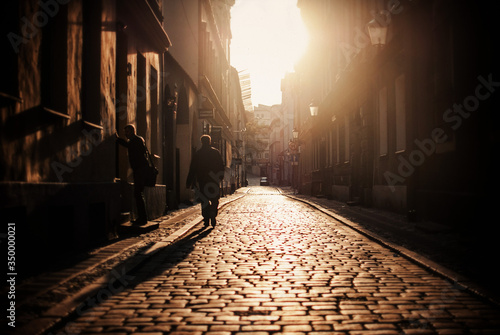 Photo Men On Cobbled Street Amidst Buildings In City