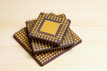 Stack Of Computer Microprocessors With Gold Contacts On A Wooden Background. Central Processing Unit. Concept Of Recycling Radio Components To Produce Gold.