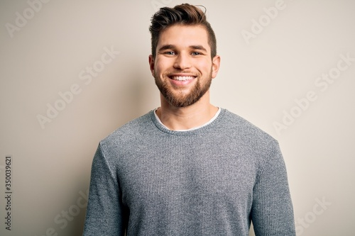 Fotografia Young handsome blond man with beard and blue eyes wearing casual sweater with a happy and cool smile on face