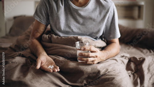 Photo Sick man with a glass of water and pills on the bed, Taking medication to allevi