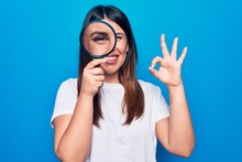 Young Beautiful Brunette Woman Using Magnifying Glass Over Isolated Blue Background Doing Ok Sign With Fingers, Smiling Friendly Gesturing Excellent Symbol