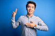 Young handsome chinese man wearing casual shirt standing over isolated blue background smiling swearing with hand on chest and fingers up, making a loyalty promise oath