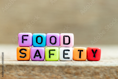 Fototapeta Colorful bead with black letter in word food safety on wood background obraz