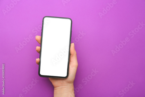 Fototapeta Female hand with mobile phone on color background