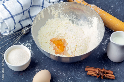 Fototapeta Flour with egg in a metal bowl among ingredients and utensils for cooking cake (flour, egg, milk, sugar, rolling pin, towel) on dark table. The concept of making dough for baking. Close up obraz na płótnie