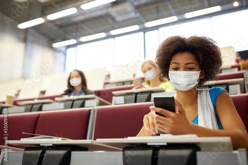 education  healthcare and pandemic concept - african student girl wearing face protective medical mask for protection from virus disease with smartphone at lecture