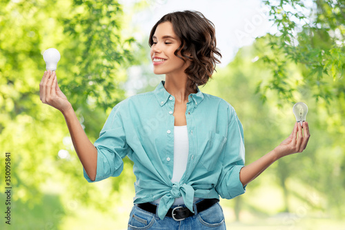 eco living, inspiration and sustainability concept - portrait of happy smiling young woman in turquoise shirt comparing energy saving light bulb with incandescent lamp over green natural background