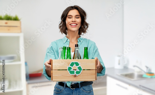 recycling, waste sorting and sustainability concept - smiling young woman holding wooden box with glass bottles and jars over home kitchen background