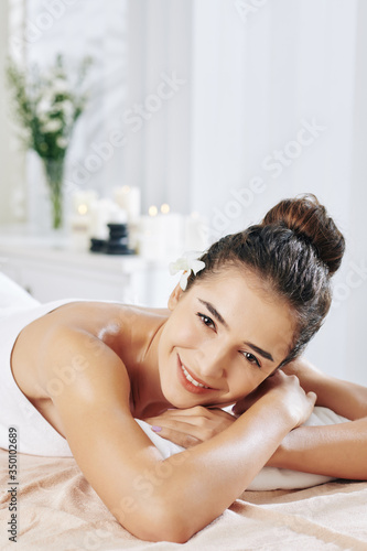 Happy pretty young woman enjoying relaxing procedures in spa salon