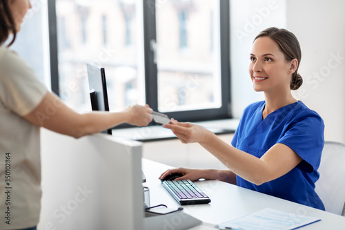 medicine, people and healthcare concept - happy smiling female doctor or nurse and patient with insurance or credit card card at hospital
