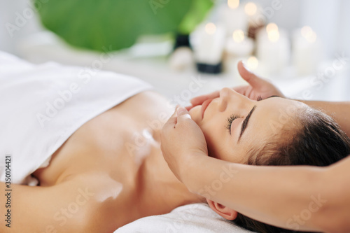 Young woman enjoying facial beauty treatment in spa salon and getting lifting massage