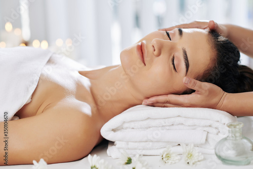 Beautician massaging face of young woman relaxing on fresh soft towels in beauty salon