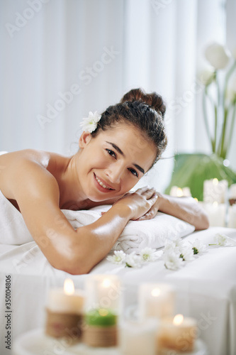 Happy young woman with flower in her hair smiling at camera after getting back massage
