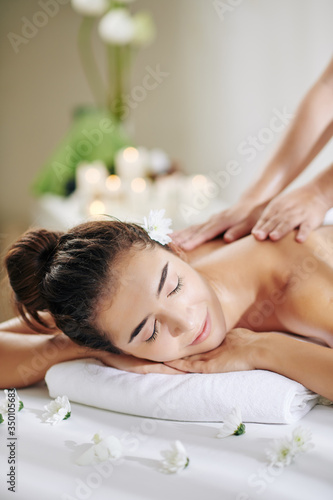 Beautiful young woman getting professional back massage in spa salon with moisturizing oils