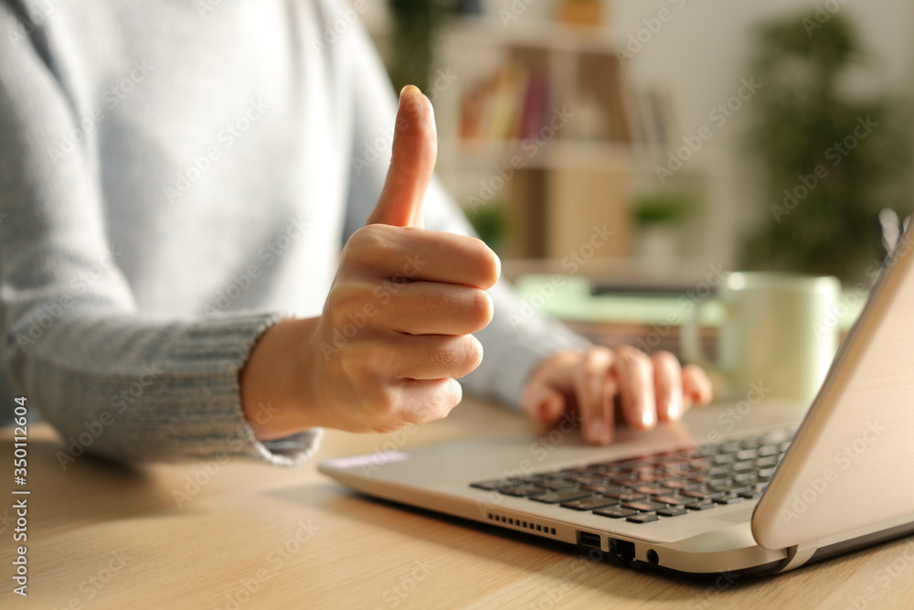 Fototapeta Woman hands with thumbs up using laptop at night