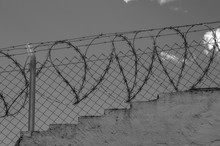 Low Angle View Of Heart Shape Barbed Wire Over Chainlink Fence Against Sky