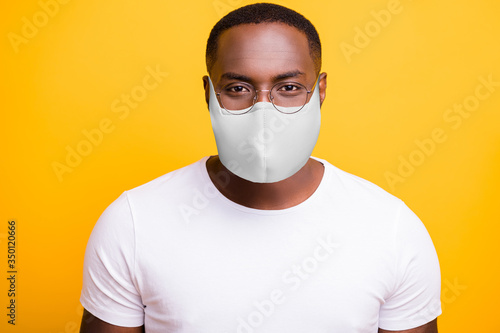 Fototapeta Closeup photo of american man look at camera quarantine social safety epidemic concept wear t-shirt protective respiratory flu facial mask isolated bright yellow background obraz
