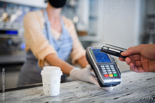 Fototapeta Contactless payment with debit card, coffee shop open after lockdown. obraz