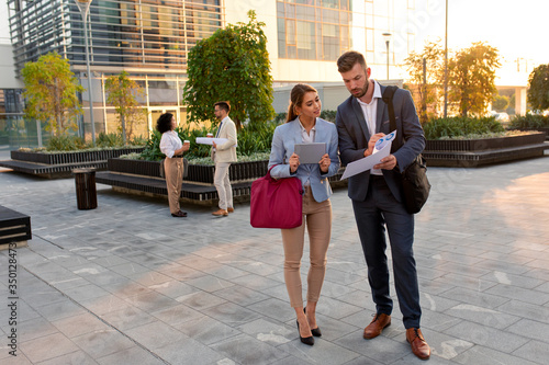 Two coworkers standing outside in front of office buildings discuss about business plan and looking at tablet.
