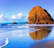 Large Rock On Beach Against Sky