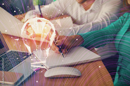 Double exposure of bulb drawing over people taking notes background. Concept of idea