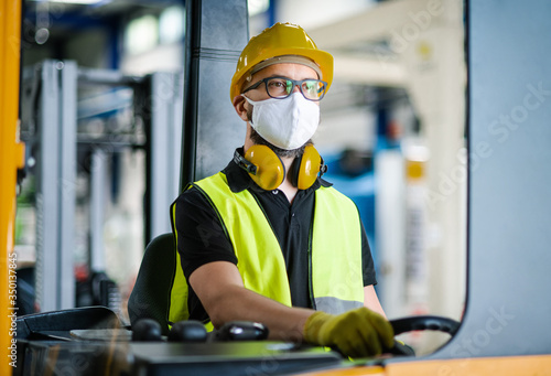Obraz Man worker forklift driver with protective mask working in industrial factory or warehouse. - fototapety do salonu