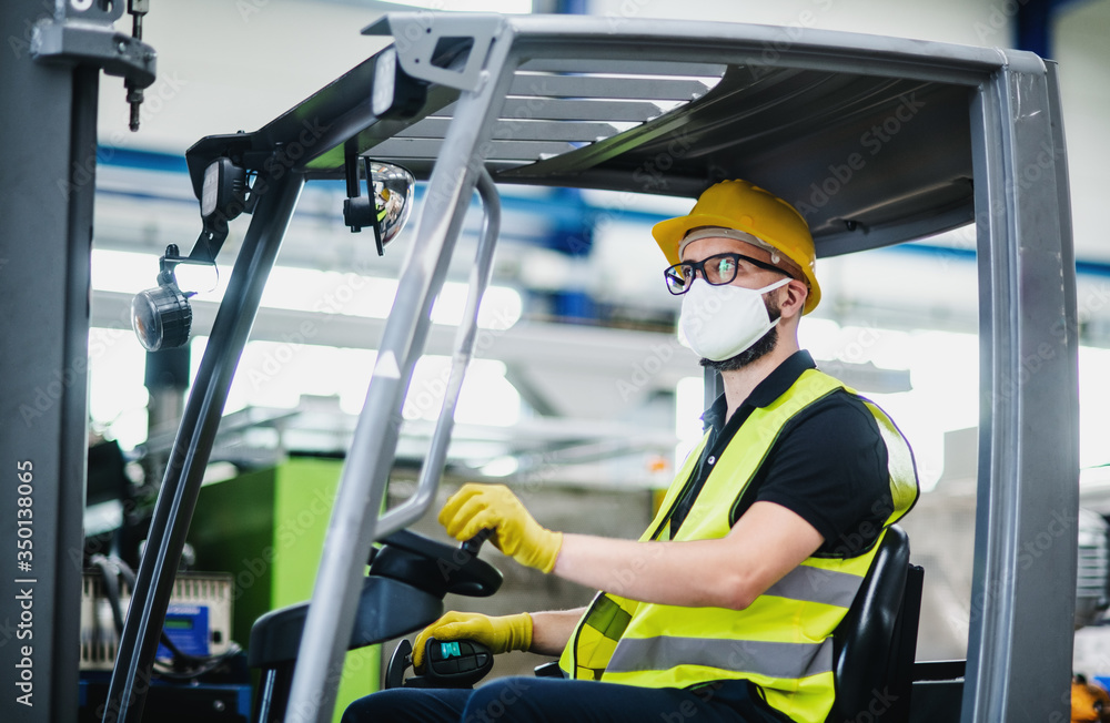 Fototapeta Man worker forklift driver with protective mask working in industrial factory or warehouse.