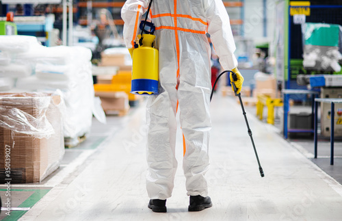 Papel de parede Man worker with protective mask and suit disinfecting industrial factory with spray gun