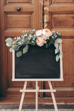 Blank Wedding Chalkboard Sign Mockup Scene. Wooden Easel With Welcome Board. Floral Garland Of Green Eucalyptus Branches And English Roses Flowers. Rustic Birthday Party Decoration. Blurred Old Door.