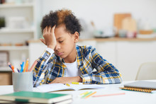 Portrait Of Tired African-American Boy Falling Asleep At Desk While Doing Homework, Copy Space
