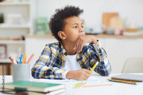 Fotografie, Obraz Portrait of teenage African-American boy daydreaming at desk while doing homewor