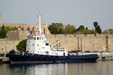 Marine Ship At The Walls Of A Medieval City, In The Port Of The Island.against The Background Of Stone Walls, The Palace Of Masters, Knights