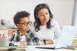 Leinwandbild Motiv Portrait of cute African boy wearing big glasses while using laptop with mom, homeschooling and remote education concept
