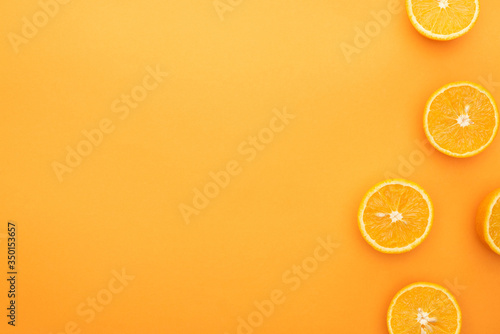 Fototapeta top view of juicy orange slices on colorful background obraz