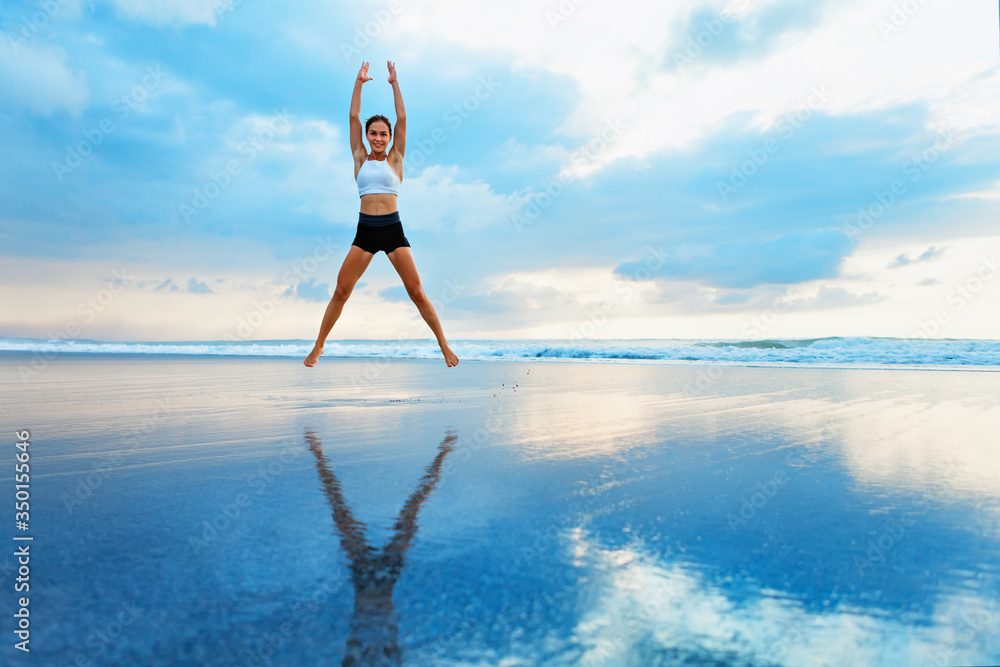 Fototapeta Young woman doing jumping jack or star jumps exercise to burn fat, keep fit. Sunset beach, blue sky background. Healthy lifestyle at training camp, outdoor fitness activity, family summer holiday.