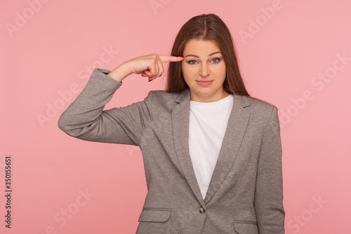 фотографія This is insane idea! Portrait of woman in business suit showing stupid gesture with finger at her temple, displeased with reckless silly joke, out of mind