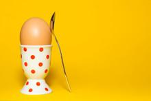 Ei In Einem Eierbecher Mit Einem Löffel Isoliert Vor Gelbem Hintergrund, Hühnerei