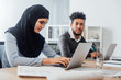 canvas print picture - Selective focus of arabic businesswoman using laptop near african american colleague in office