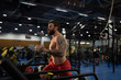 Bearded sportsman running on treadmill in gym