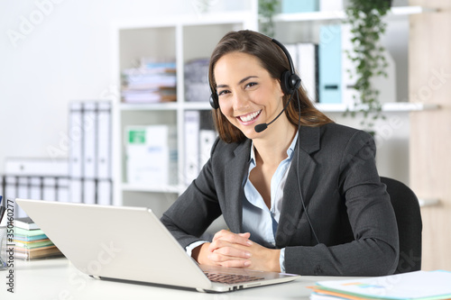 Happy telemarketer posing looking at camera at office Canvas Print