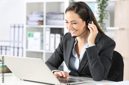 Happy telemarketer with laptop attending call at office Wallpaper Mural