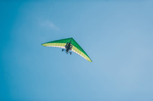 The Motorized Hang Glider In The Clear Blue Sky