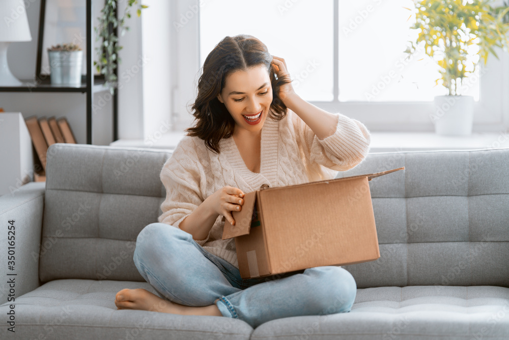 Fototapeta woman is holding cardboard box sitting on sofa at home