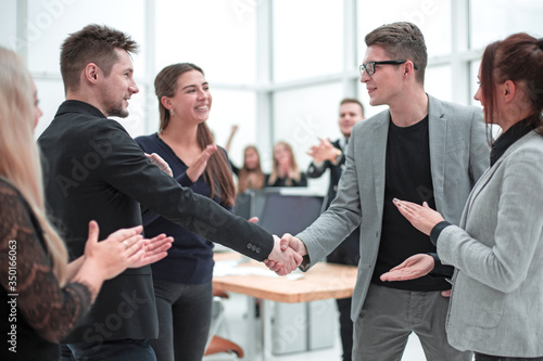 business partners shaking hands to the applause of the working group Canvas Print